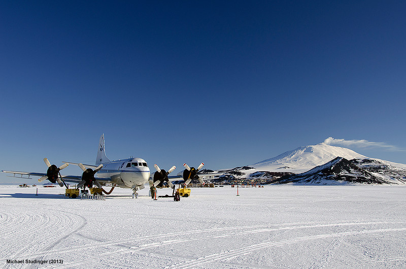 NASA's P-3 Orion research aircraft is parked on the sea ice runway in McMurdo Sound, Antarctica. Mt. Erebus, the southernmost active volcano on earth, and McMurdo Station can be seen in the background.