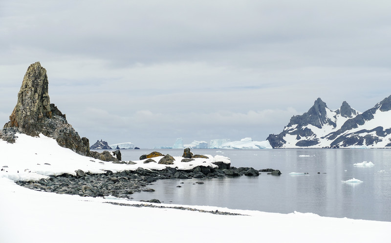 Snow, rocky peaks and an icy bay in Antarctica with icebergs in the distance.