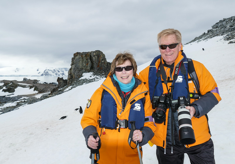 Senior travelers pose on the snow at Half Moon Island in Antarctica.