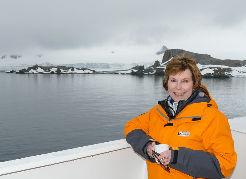 Boomer woman sips a cup of hot chocolate before going on a Seabourn excursion to Half Moon Island in Antarctica.