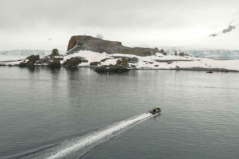 A zodiac motors toward a rocky escarpment on Half Moon Island, Antarctica