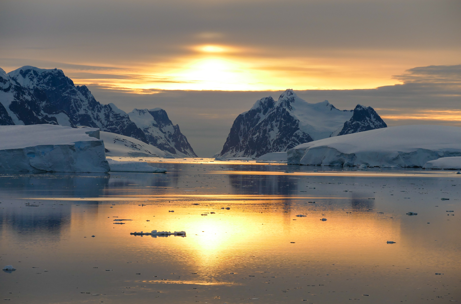 Sunset in between snow-covered mountains taken from a boat in an Antarctica channel.