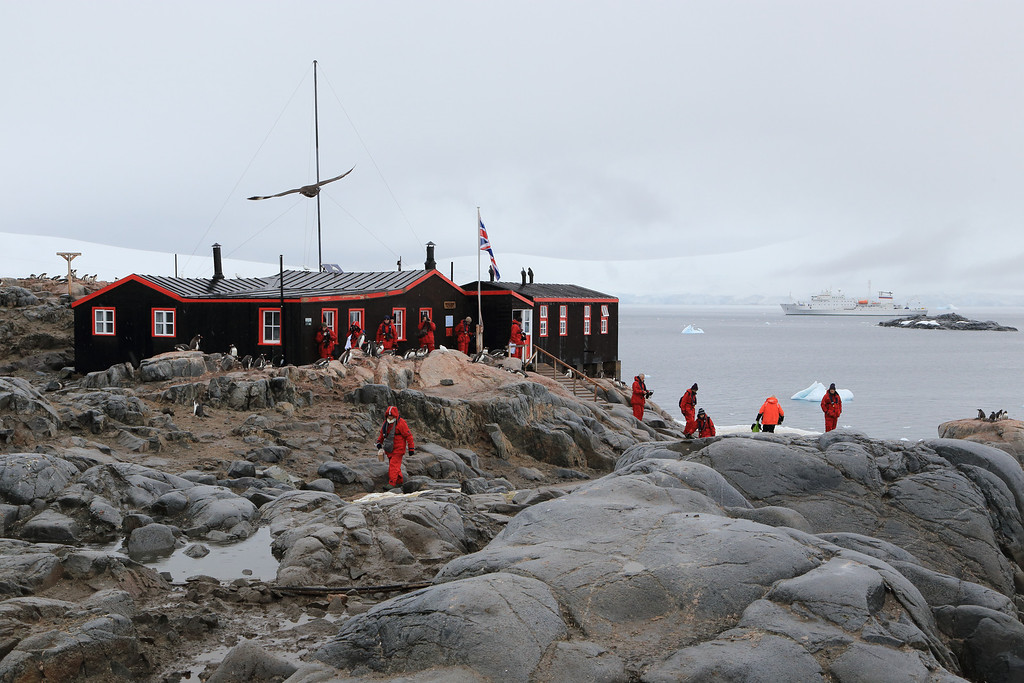 """Historic British Base A, Port Lockroy on Goudier Island. Also a functioning UK Post Office for visitors, fun to send postcards from there, to see when they will arrive!  Sergey Vavilov in the background.<br /> <br />  <a href=""""http://www.ats.aq/siteguidelines/documents/Goudier_e.pdf"""">http://www.ats.aq/siteguidelines/documents/Goudier_e.pdf</a>"""