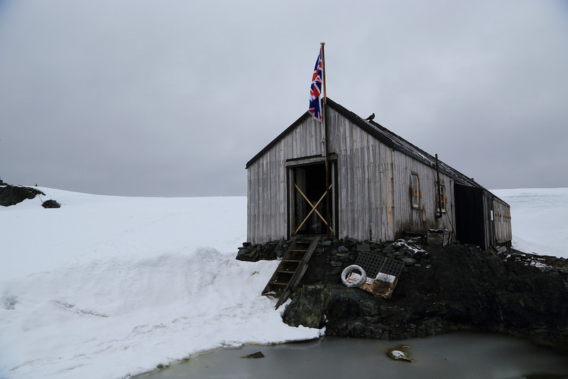 "South of the Antarctic Circle,  Detaille Island, British scientific base ""W"" of the late 1950s at 66˚52'S, 66˚48'W  The OOE crew delivered supplies (some shown)  to the two occupants who are living here during the summer months.  It's also a UK Post Office. Mail from here is sent to the Falklands and then onto the UK for forwarding.