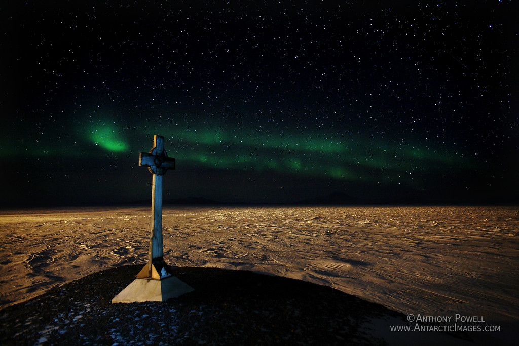 Vince's Memorial Cross, Hut Point, Ross Island, Antarctica. Aurora Australis in the background. The snow is being lit up from the lights of McMurdo Station.