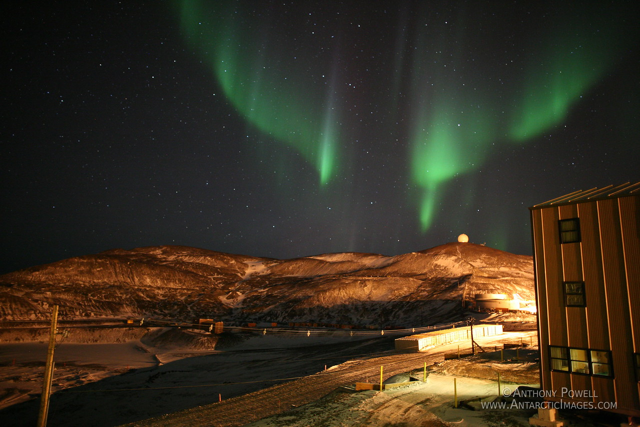 Looking north behind McMurdo Station, an aurora hangs in the sky above the dome that houses the NASA satellite ground station on the ridge.