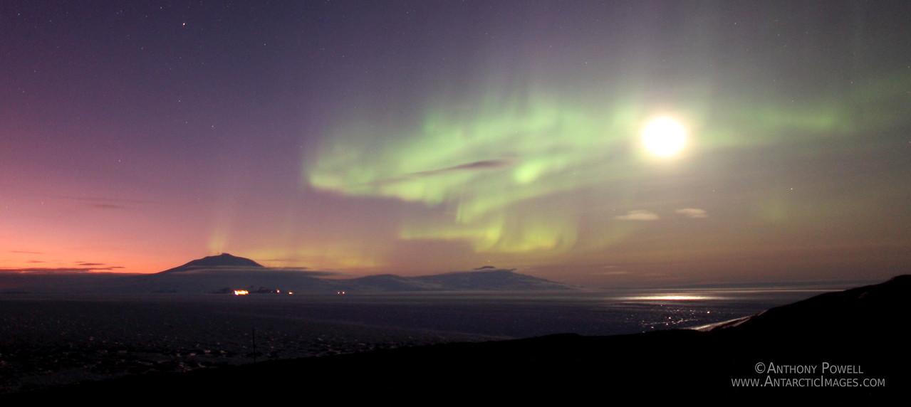 Moon and Auroras over Ross Island as seen from Black Island. The lights of McMurdo, Scott Base, and some vehicles from the bases can be seen in front of Mount Erebus.