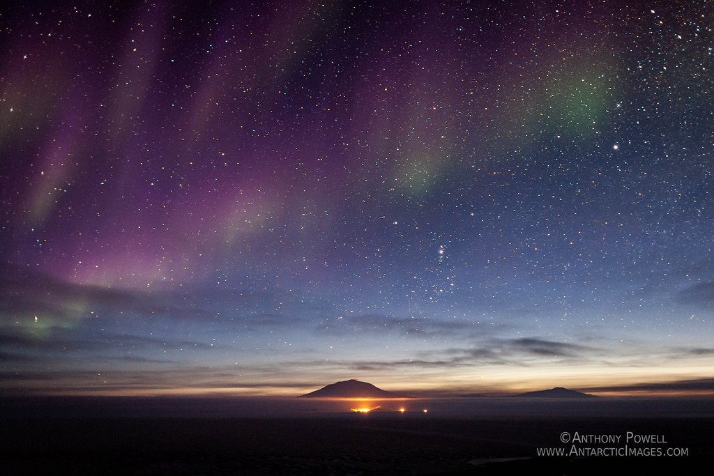 Looking North from Black Island towards Mount Erebus. The lights of McMurdo Station and Scott Base in the foreground. If you zoom in on the summit of Mount Erebus, you can see a red glow from the lava in the crater.