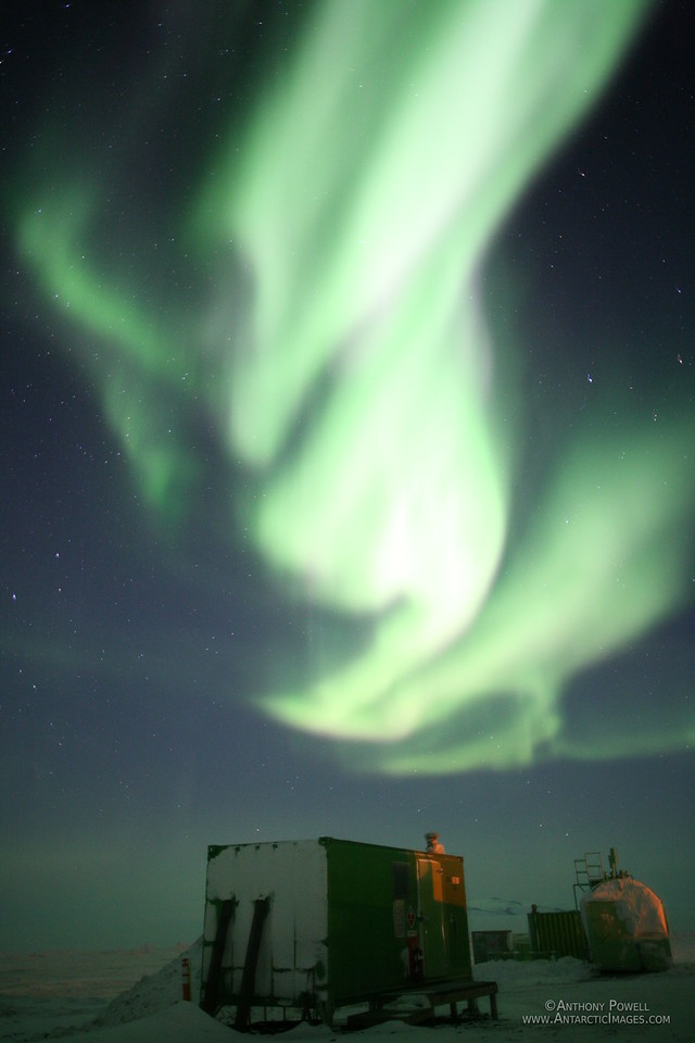 Aurora over a fishing hut at Scott Base on a winter evening