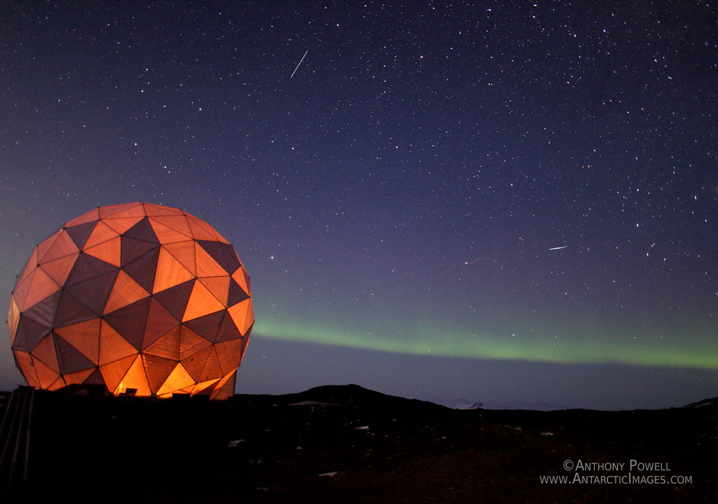 Satellite Dome lit up from within, with an aurora trailing across the horizon in the distance