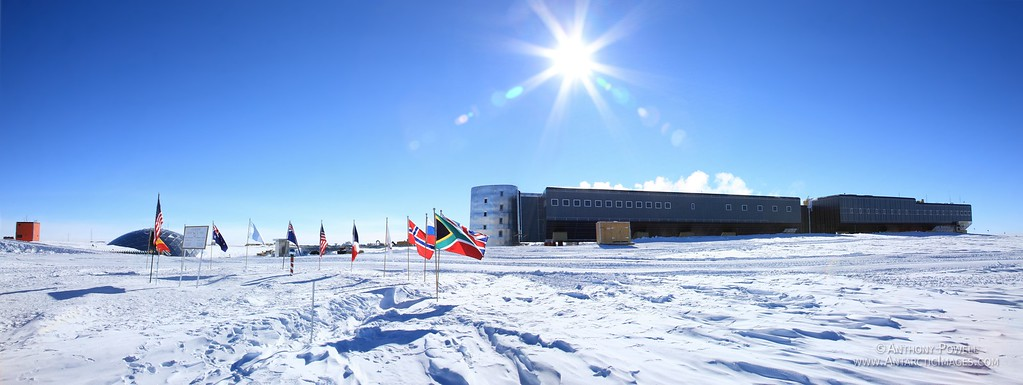 South Pole Panorama. On the left is the Geographic South Pole, plus the ceremonial marker. behind it is the dome that housed the old station. The new South Pole Station is the buildings on the right.