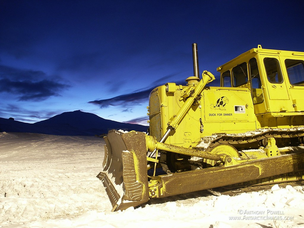 D8 bulldozer parked outside Scott Base in August, the noon glow behind Mount Erebus to the north.