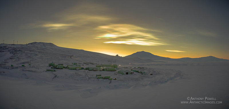 Scott Base at noon about a week before the sun is due to rise after the long dark winter. Some light nacreous clouds are in the sky above Mount Erebus.