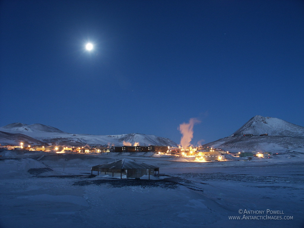 Discovery Hut with McMurdo Station in the background with the full moon in late winter.