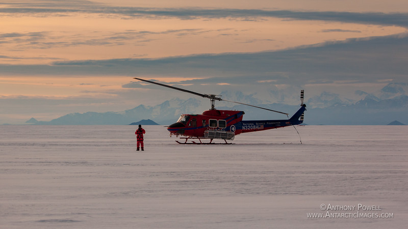 Helicopter resting on the sea ice of McMurdo Sound in the middle of the night in summer.