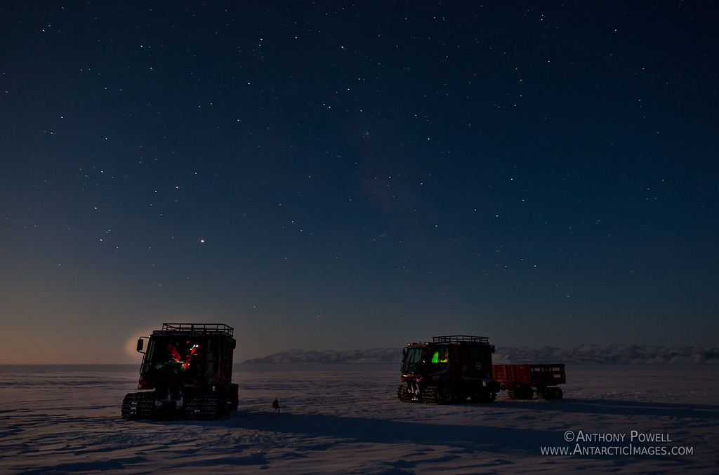 Pisten Bullies traversing across the Ross Ice Shelf under the winter full moon. Minna Bluff is in the background.