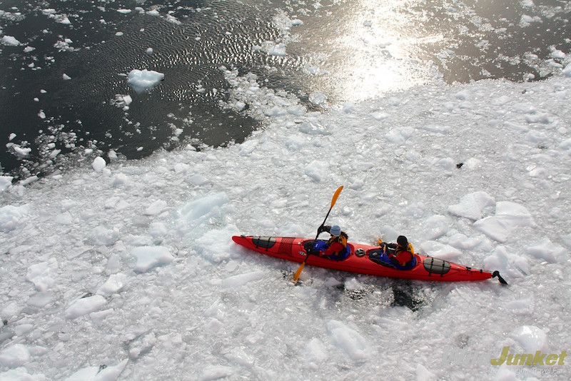 Kayakers paddling through ice