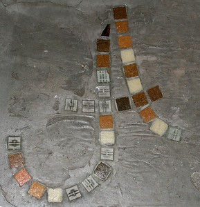 """""""A"""" stands for """"Art""""; mosaic in the concrete floor of the bathroom."""