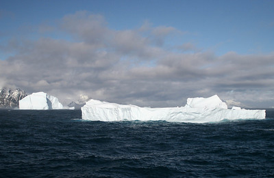 The sun is breaking through the clouds.  The icebergs look whiter in this light.