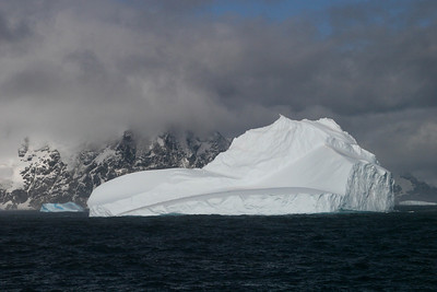 A white berg with a smaller blue berg in the distance.