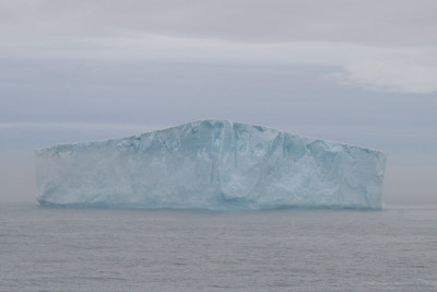 Tabular iceberg with a veil of mist running through the lower half.