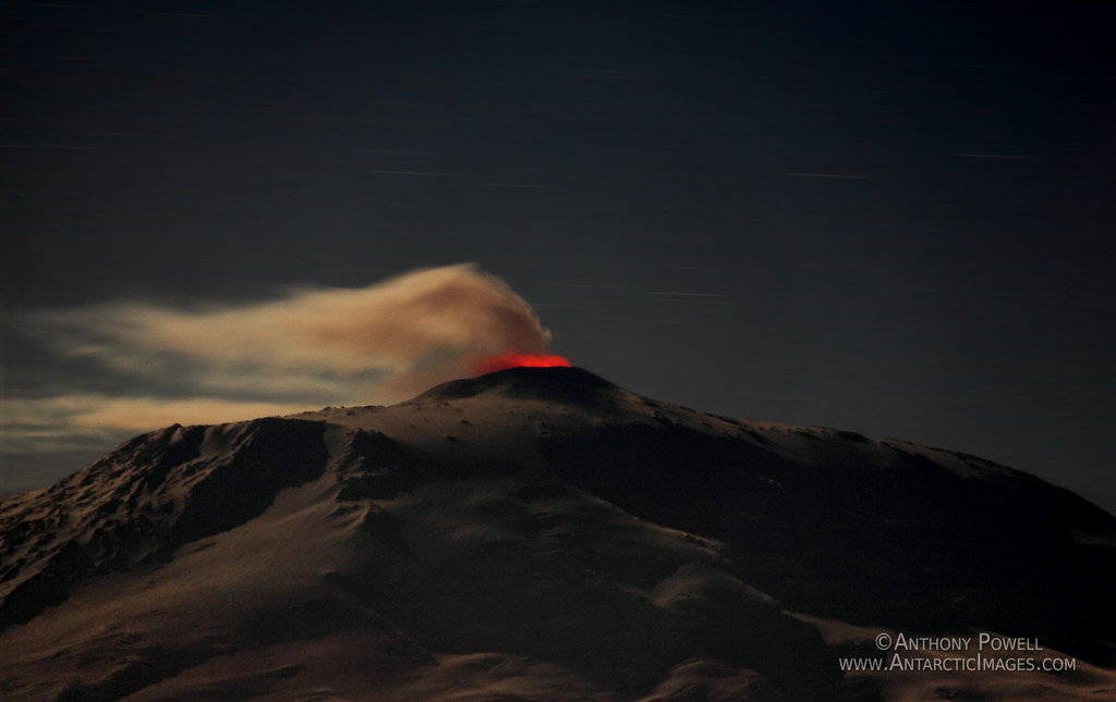 Mount Erebus glowing in the Antarctic night. The lava in the crater is lighting up the steam from underneath.