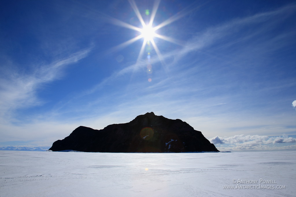 The sun over Inaccessible Island in McMurdo Sound, surrounded by seasonal sea ice.