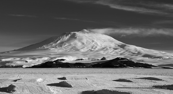 Mount Erebus black & white. McMurdo Station can be seen at the base of the mountain. The snow berms in the foreground are for storing the airfield equipment on over the winter so things don't get buried in the blowing snow.