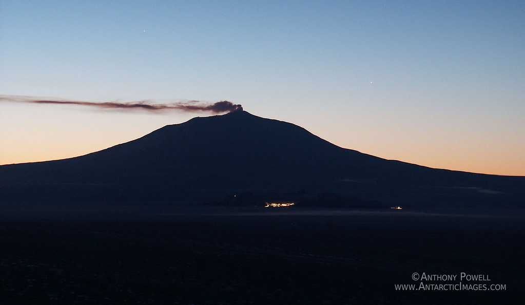 Mount Erebus, Antarctica's active volcano letting off smoke. The lights of McMurdo Station and Scott Base can be seen in the foreground.
