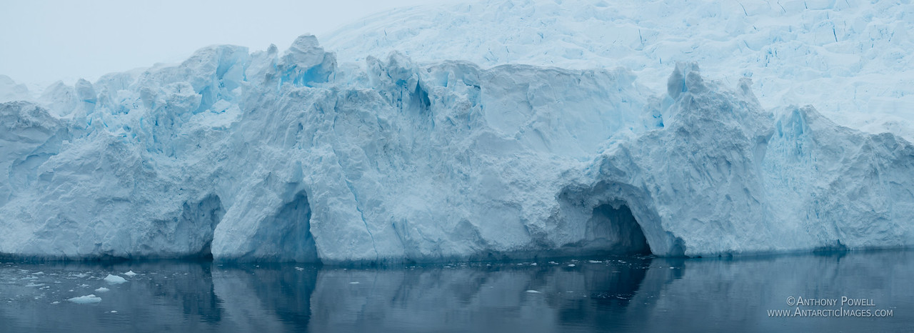 Glacier face and caves on the Antarctic Peninsula taken from the deck of the Lindblad Nat Geo Orion ship.