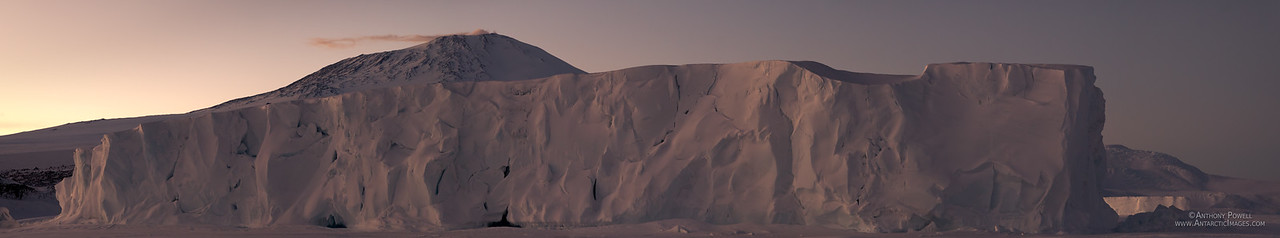Panoramic view of an iceberg stuck in the new sea ice at Cape Evans at the end of winter. Mt Erebus in the background.