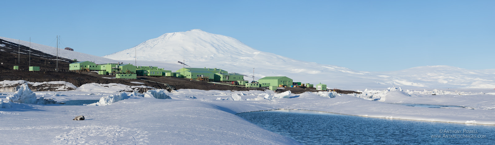 Scott Base, Mount Erebus, and melt pools forming in the sea ice in front of the base in late summer.