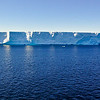 """Large """"tabular"""" iceberg. This type of flat-topped iceberg is usually formed by breaking off from an ice shelf. In the Weddell Sea areas we traveled, there were many large tabular icebergs, which came from two sections of the Larsen Ice Shelf that have broken away from their former positions along the Antarctic Peninsula.<br /> <br /> They are beautiful to behold, but an ominous sign of the effects of Global Warming."""