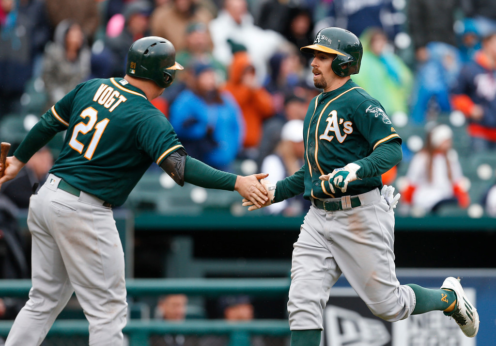 . Oakland Athletics\' Billy Burns, right, is congratulated by Stephen Vogt (21) after scoring on a Khris Davis single in the ninth inning of a baseball game against the Detroit Tigers in Detroit, Thursday, April 28, 2016. Detroit won 7-3. (AP Photo/Paul Sancya)