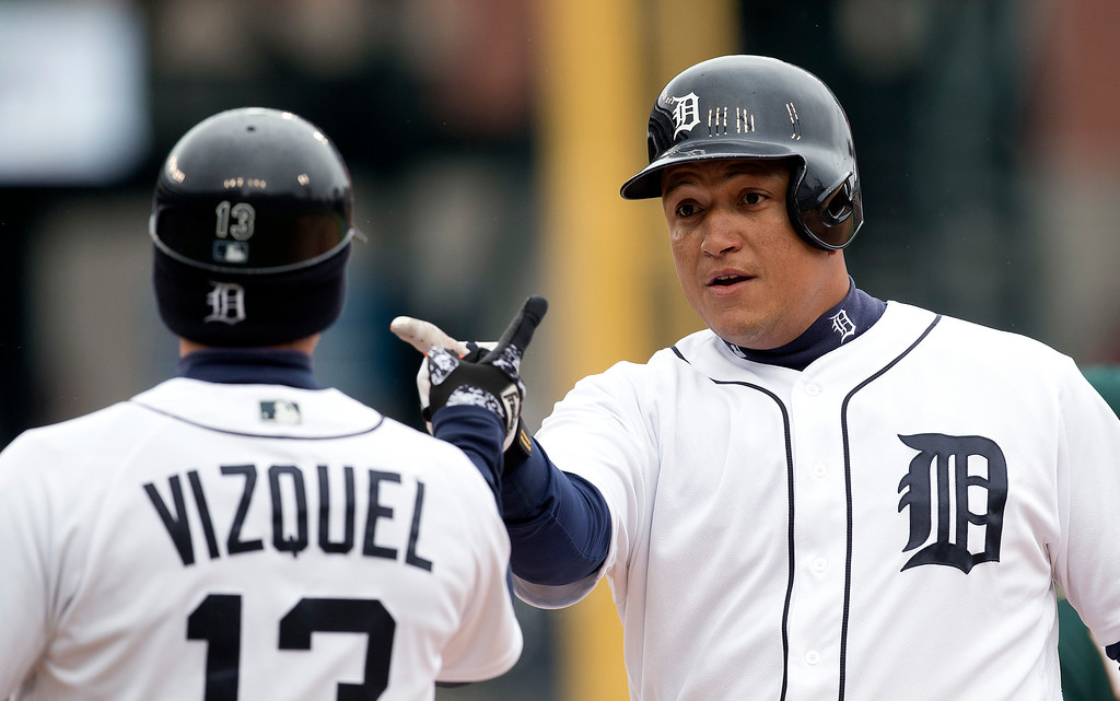 . Detroit Tigers\' Miguel Cabrera celebrates his one-run single with first base coach Omar Vizquel in the third inning of a baseball game against the Oakland Athletics in Detroit, Thursday, April 28, 2016. (AP Photo/Paul Sancya)