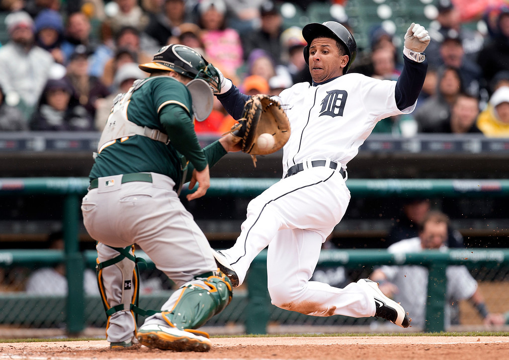 . Detroit Tigers\' Anthony Gose slides safely past the tag of Oakland Athletics catcher Stephen Vogt on a Ian Kinsler double in the third inning of a baseball game in Detroit, Thursday, April 28, 2016. (AP Photo/Paul Sancya)