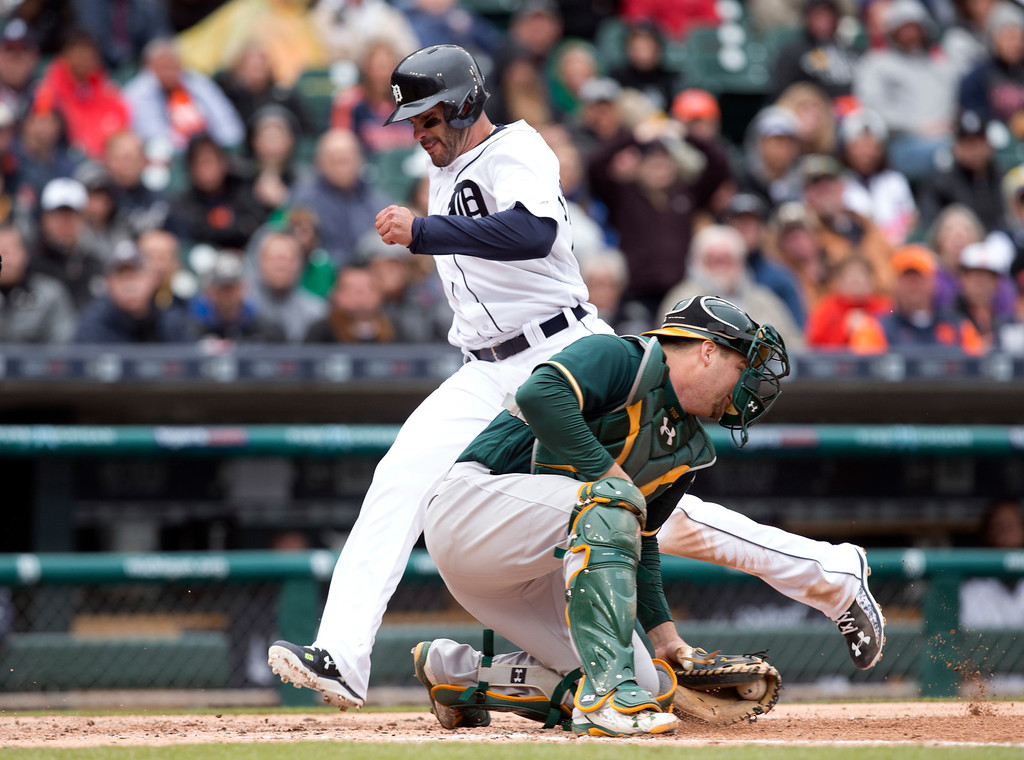 . Detroit Tigers\' J.D. Martinez scores on a Victor Martinez fly ball as Oakland Athletics catcher Stephen Vogt catches the throw in the third inning of a baseball game in Detroit, Thursday, April 28, 2016. (AP Photo/Paul Sancya)