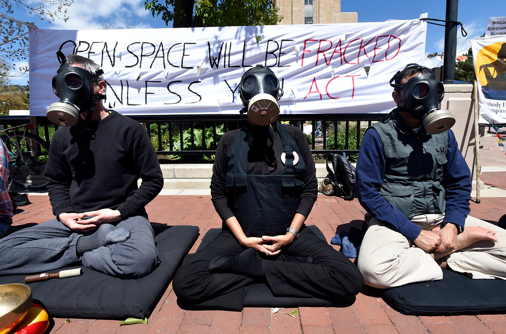 . Bill Van Eimeren, left, Kritee Kanko and Imtiaz Rangwala wear gas masks while meditating during a anti-fracking protest on Monday at the Boulder County Courthouse on the Pearl Street Mall in Boulder, Colo. For more photos and video of the fracking protest go to www.dailycamera.com Jeremy Papasso/ Staff Photographer/ May 1, 2017