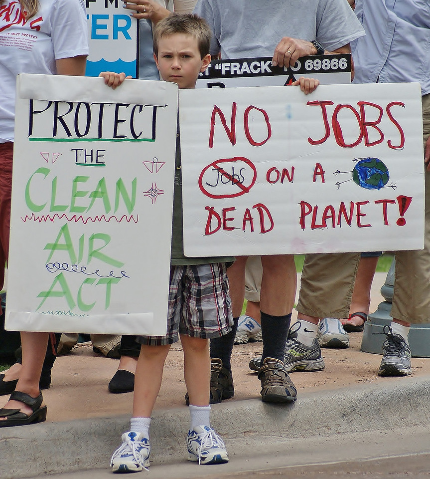 "Young boy holds sign ""No Jobs On Dead Planet"", at fracking demonstration."