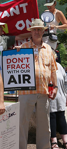 Man with sign about fracking and clean air.