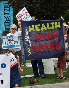 "Fracking opponents with banner ""Health Over Greed""."