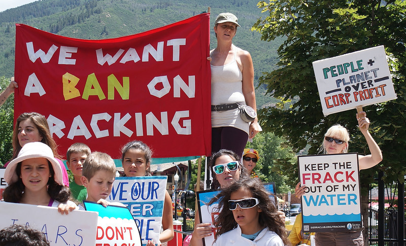 Group of anti fracking demonstrators hold signs and large banner at protest.