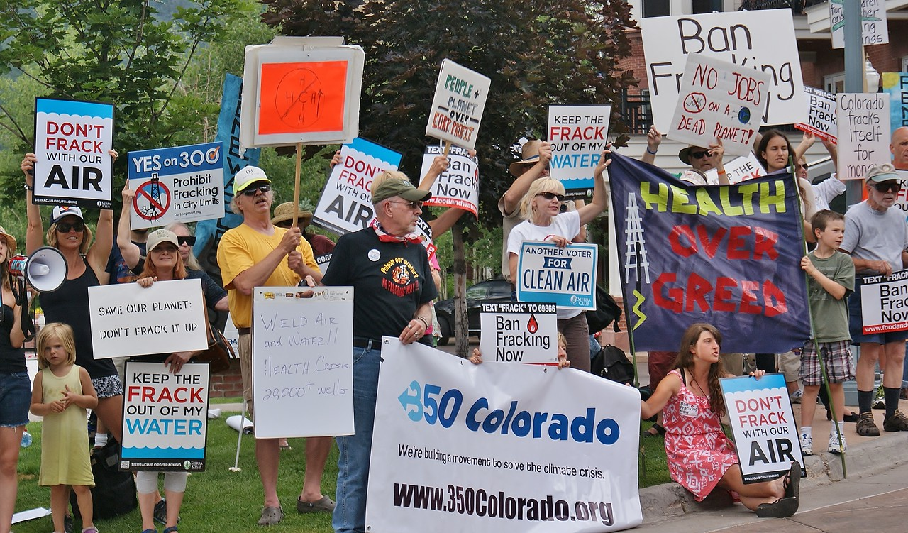 Large group of anti fracking protesters with many signs.