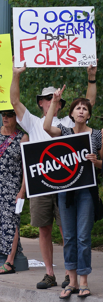 Woman with no fracking sign raises hand and shouts.