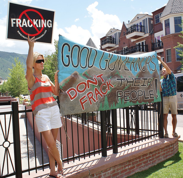 man and woman hold large  anti fracking banner  directed at Governors conference attendees.