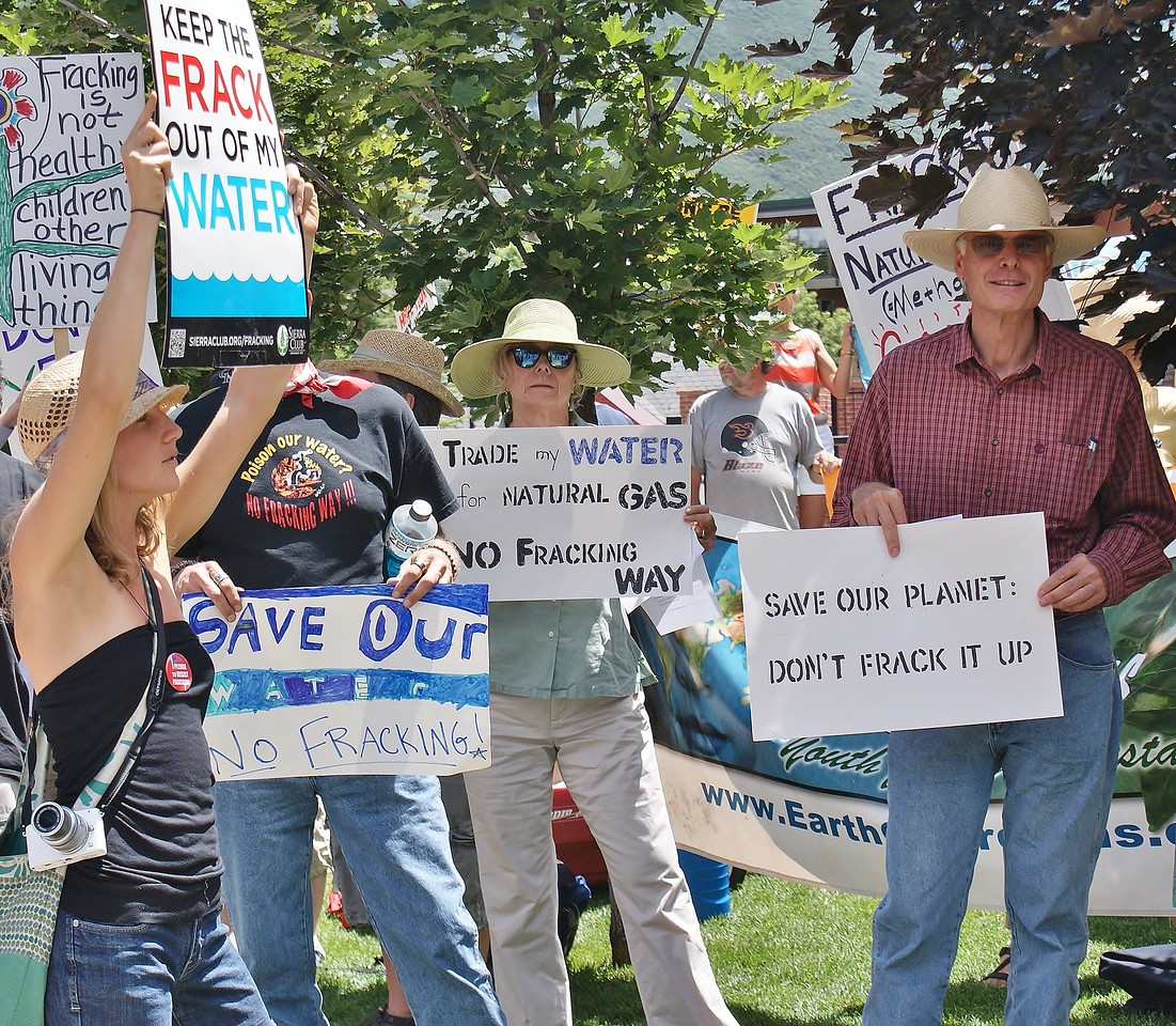 Group of fracking opponents holding signs at demonstration.