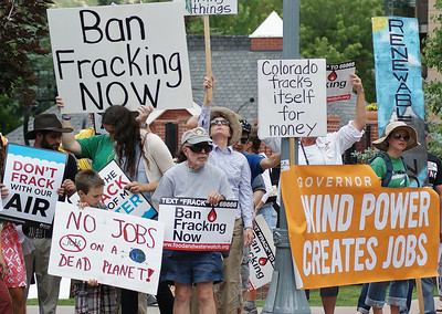 Anti fracking protesters with signs and banners including one about wind power and jobs.