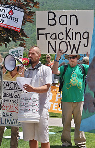 Man speaks through bullhorn  as anti fracking protesters holds sign behind him.