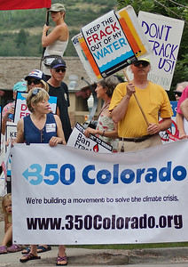 Opponents of fracking with signs, standing behind 350 Colorado banner.