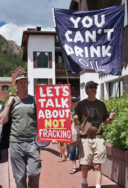 Anti fracking protesters holding signs and large banner at demonstration.